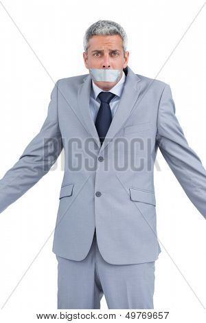 Businessman with adhesive tape on mouth on white background