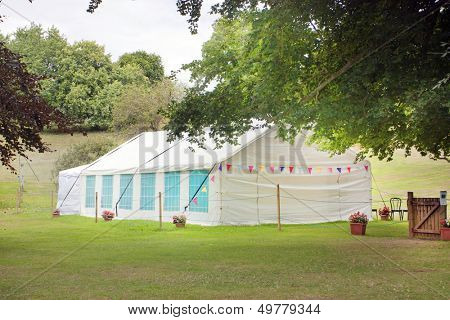 summer garden with a marquee tent on the grass