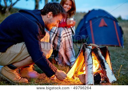 Young man kindling firewood in the countryside with girl and tent on background