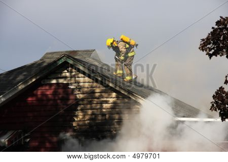 Fireman On Top Of A Burning House