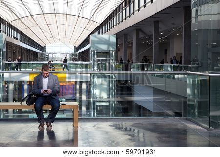 VALENCIA, SPAIN - FEBRUARY 12, 2014: A businessman checks his smart phone at the 2014 Feria Habitat Valencia Trade Fair in Valencia.