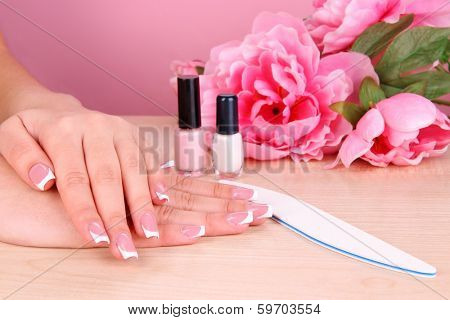Beautiful woman hands with french manicure and flowers on table on pink background