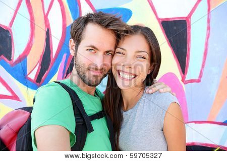 Happy couple selfie selfportrait in front of Berlin Wall, Berlin, Germany. Beautiful young interracial couple looking at camera having fun on Europe travel. Asian woman, Caucasian man.
