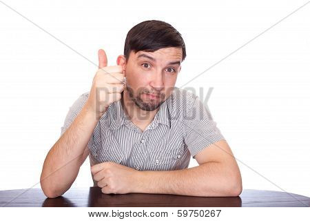 young casual man sitting with legs crossed and showing both thumbs up to the camera