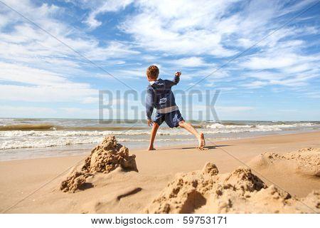 Boy throwing rocks into the lake