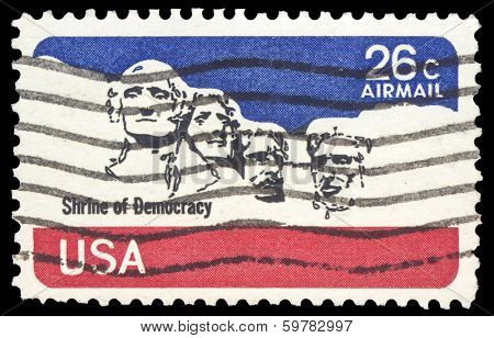 USA-CIRCA 1974: A 21 cent US Airmail  stamp, shows image of Mount Rushmore with  iconic faces of  , George Washington, Thomas Jefferson, Theodore Roosevelt, and Abraham Lincoln, circa 1974.
