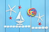 Sea shell, lollipop candy and decorative sailing boat abstract over wood background. poster