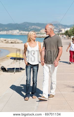 Casual Middle-aged Couple Walking At The Coast