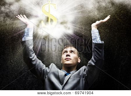 Businessman looking at shining dollar symbol above