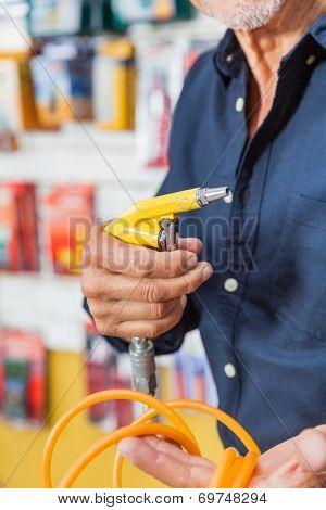 Cropped image senior man holding air compressor hose in hardware shop