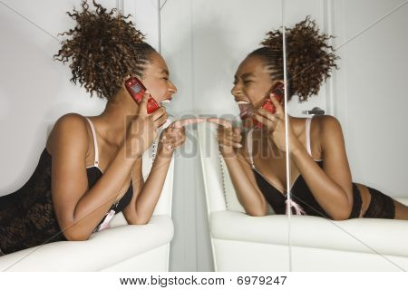 Attractive Young Woman Holding Cell Phone And Laughing