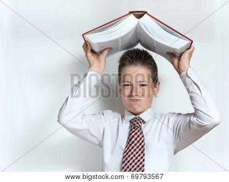 Displeased schoolboy throws big book