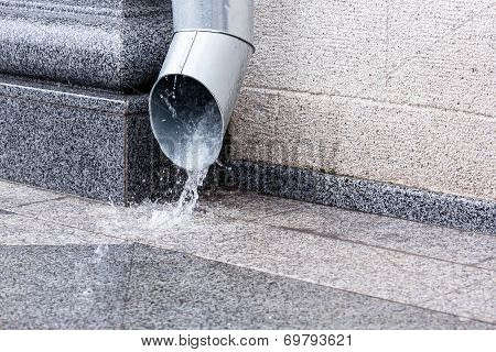 Rain water flowing from a metal downspout during a heavy rain poster