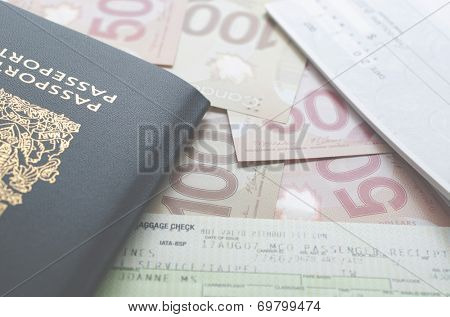 Coquitlam, BC, Canada - July 24, 2014 : Canada passport with boarding pass and money on the table.  All Canadian passports are issued by Passport Canada.