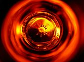 Reflection of a campfire through the glass of an amber beer bottle poster