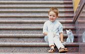 cute kid and small kitten sitting on stairs poster