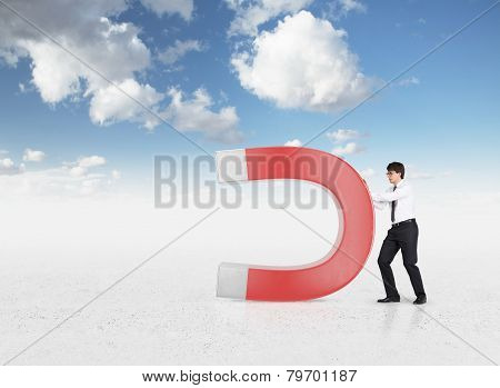 businessman holding large red magnet close up poster