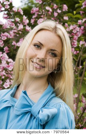 Beautiful blonde young woman in blue blouse