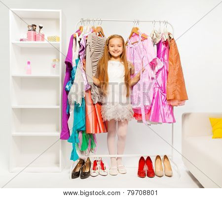 Cute girl among colorful bright dresses, clothes