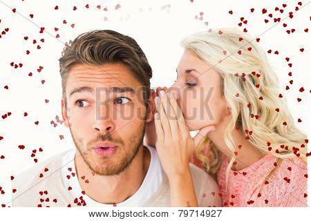 Attractive blonde whispering secret to boyfriend against red love hearts