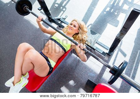 Woman at bench press in gym exercising for better fitness poster