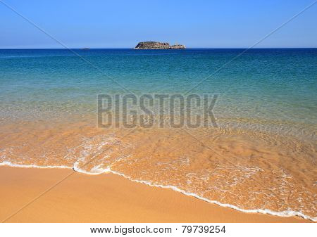 Turquoise sea washing onto deserted Algarve beach.