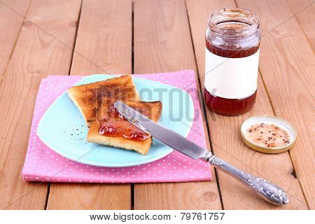 Toast bread spread with jam on plate and napkin with knife near jar on wooden table background
