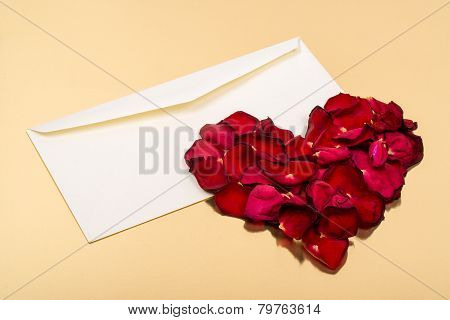 Heart Of Red Petals Lying On Top Of An Open Blank Envelopes
