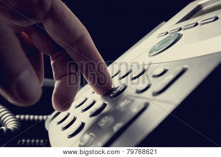 Person Dialing Out On A Telephone