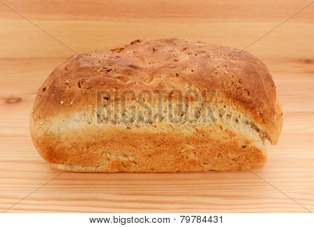 Freshly baked loaf of crusty bread on a wooden kitchen table poster