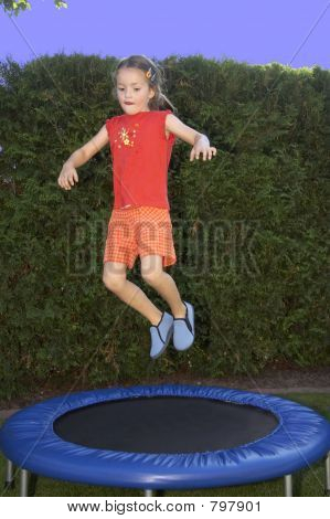 young girl jumping on trampoline