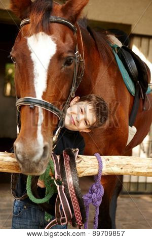 Happy little boy caressing horse, smiling, looking at camera.