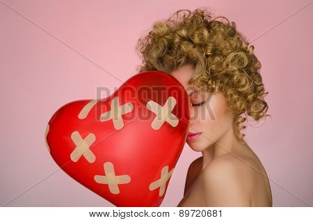 Unhappy Young Woman With Ball In Shape Of Heart