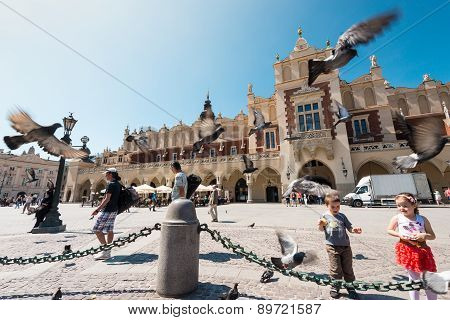 Children And Tourists At Square In Krakow Poland.