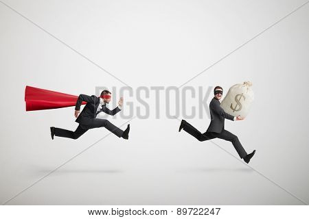 thief stole the bag with money and running away from superman over light grey background