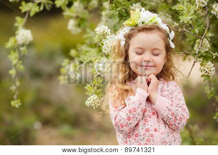 Portrait of little girl outdoors in a lush garden.