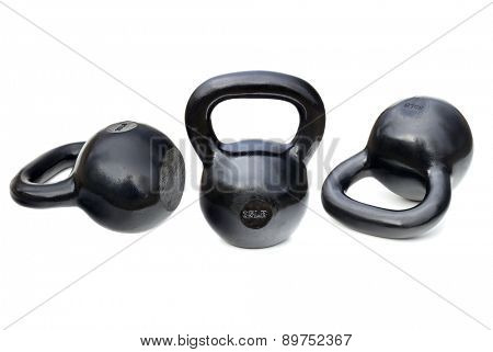 three black shiny 35 lb iron kettlebells for weightlifting and fitness  training isolated on white with clipping paths