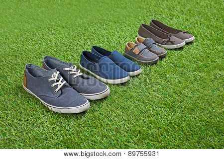 Family shoes standing  on green summer grass