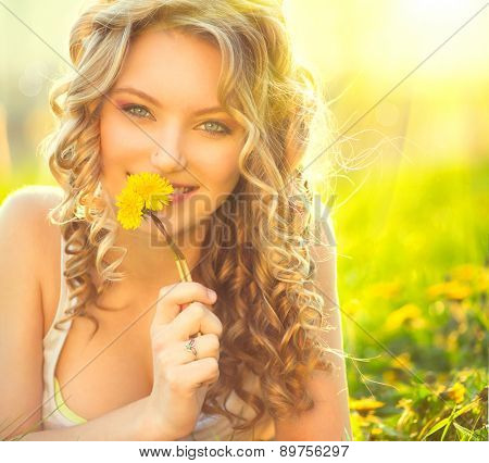 Beauty blond model girl lying on a field and smelling dandelion flowers. Allergy free. Beautiful Young Woman in the Meadow.  Outdoors. Enjoy Nature. Healthy Smiling Girl portrait