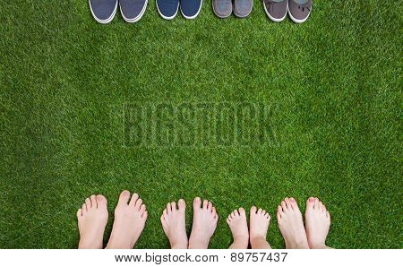 Family legs standing with shoes on green grass