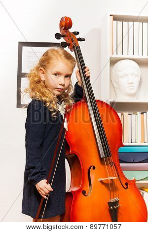 Girl with curly hair holds string to play cello