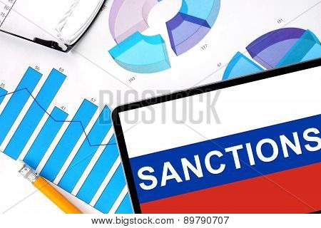 Tablet with word sanctions on the Russian flag and graphs.
