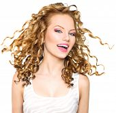 Beauty model girl with blowing Blonde curly hair. Portrait isolated on white background. Healthy wavy hair. Hairstyle. Beautiful smiling young woman. Beautiful face, natural make up. Long permed hair poster