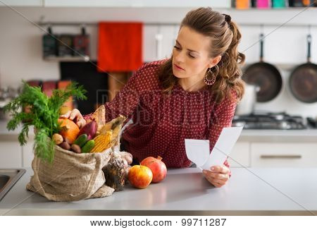 Woman In Kitchen Holding Shopping List Looking Through Items