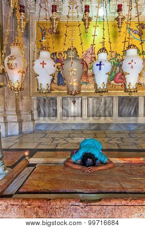 JERUSALEM. ISRAEL - JULY 26, 2015: Prayer at Stone of Anointing at the entrance to the Church of the Holy Sepulchre in Jerusalem - the place where Jesus' body was prepared for burial.