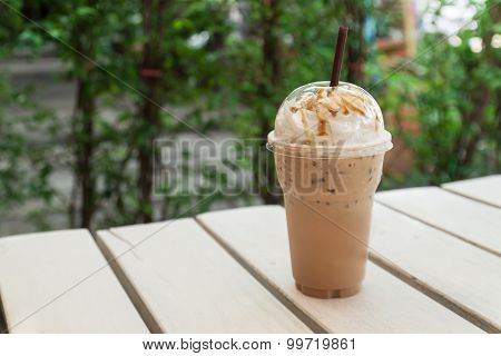 Iced coffee in plastic cup on table