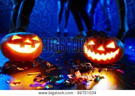 Pumpkin lanterns on floor among confetti