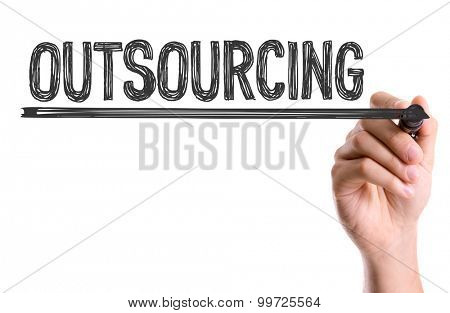 Hand with marker writing the word Outsourcing