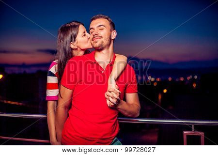 Beautiful young couple in love after sunset