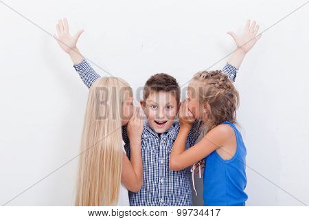 Teenage girls whispering in the ears of a secret teen boy on white background poster